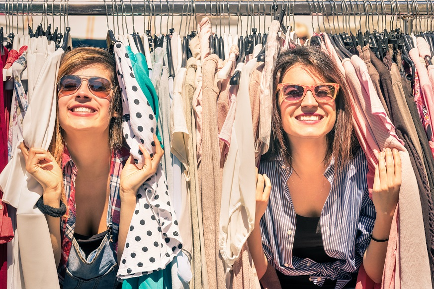 Women poking their head through clothes rails